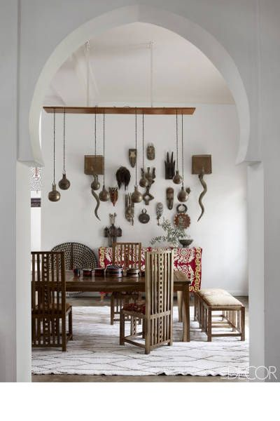 In the dining room of writer and human-rights specialist Maryam Montague's Marrakech, Morocco, home, a collection of African masks hangs on the wall with a pair of horn sconces; the custom-made dining chairs are inspired by Charles Rennie Mackintosh and Frank Lloyd Wright, the suzani is from Uzbekistan, and the Berber rug is vintage.