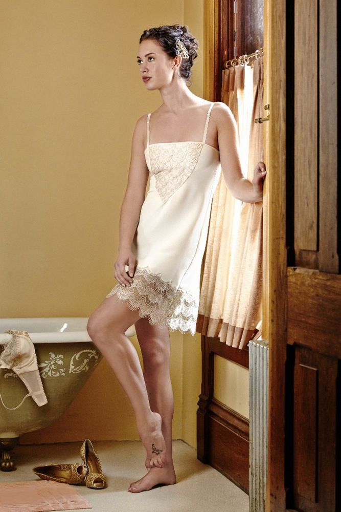 I'm so excited to be introducing true silk luxury slips to the collection this season! Perfect to wear peeking out under your favorite dresses or simply for lounging around the house in style! The Century Girl slip is made of a lightweight natural white silk crepe with a thin crinkled texture and a slight stretch. The hemline is decorated with a wide panel of gold accented American-made scalloped eyelash lace, which is also detailed across the front chest over a peach silk compl...