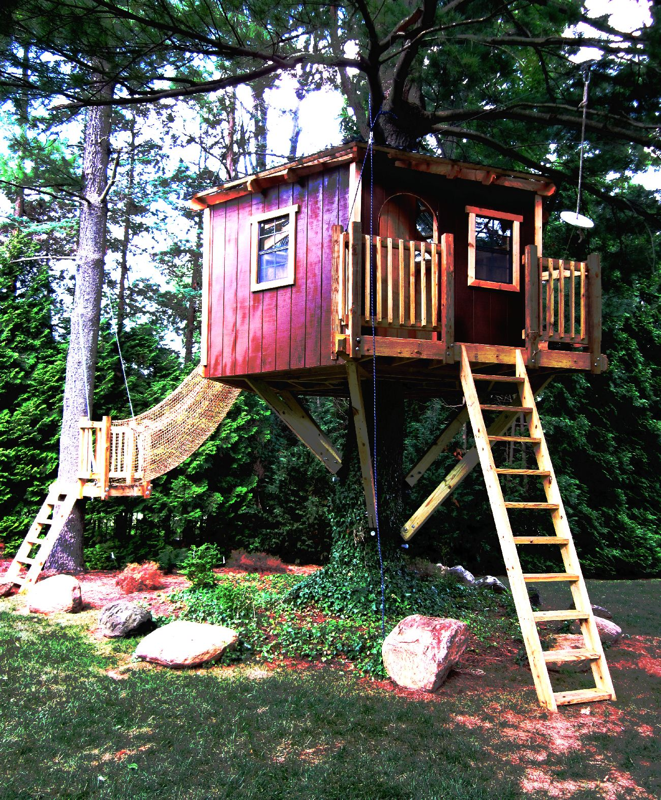 a fancy hexagonal tree house with a zip line and net tunnel tree