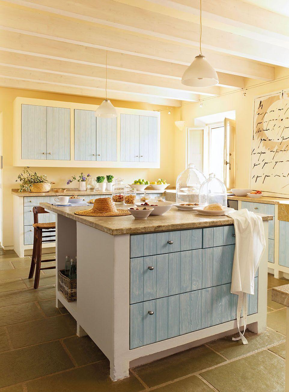 Cocina de piedra y madera azul con isla y un gran cuadro en la ...