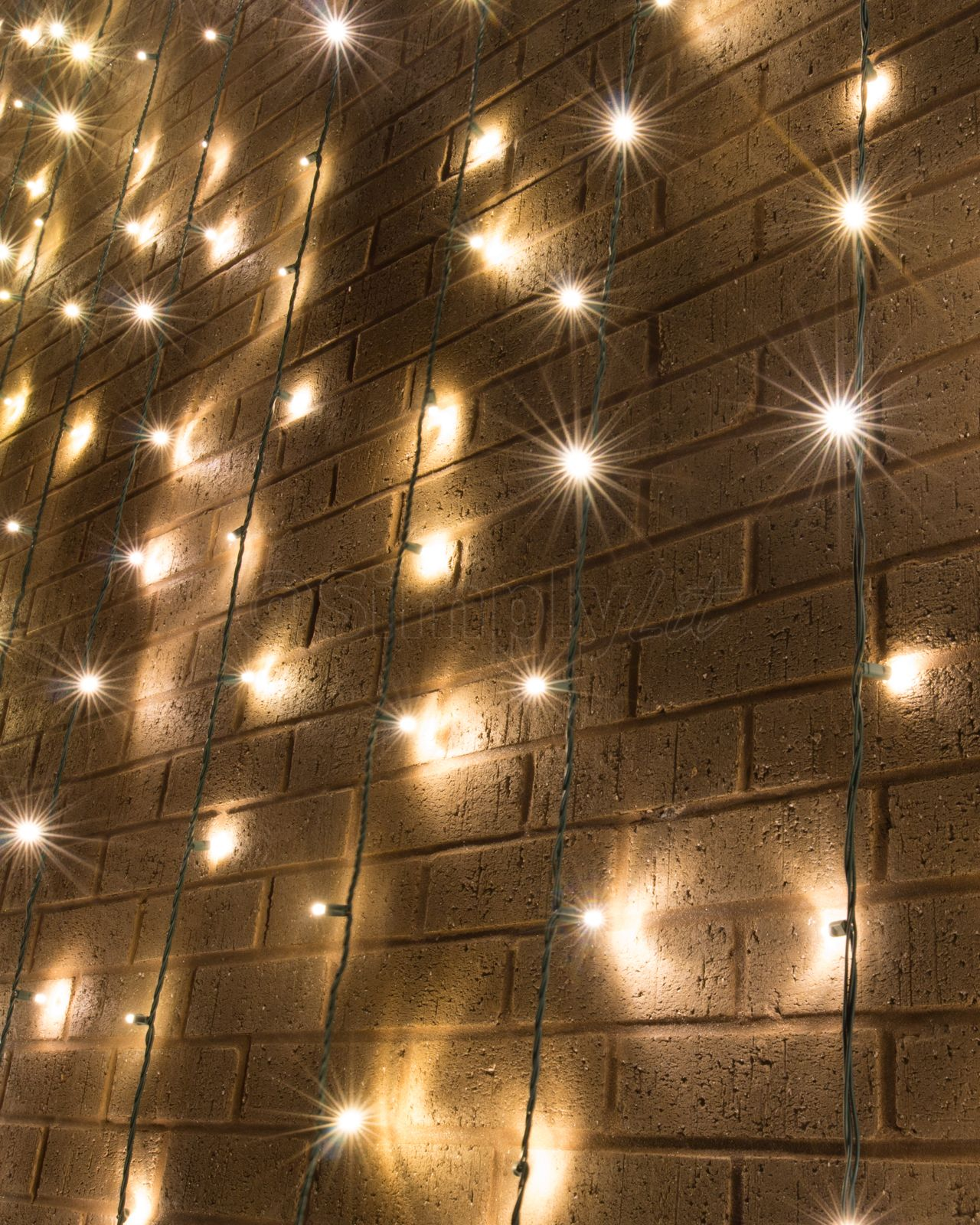 Another Close Up Shot Of The Mini Lights Overlaying A Brick Wall