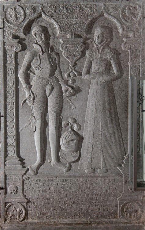 """Mygdal kirke: Gravsten i kor · Christoffer Lunge var ejer af """"Odden"""". Det var ham, som lod kapellet bygge og skænkede klokken til kirken. I montren længst til højre findes en kårde, der lå på hans kiste.  Stenen lå oprindelig over gravhvælvingen i gravkapellet."""