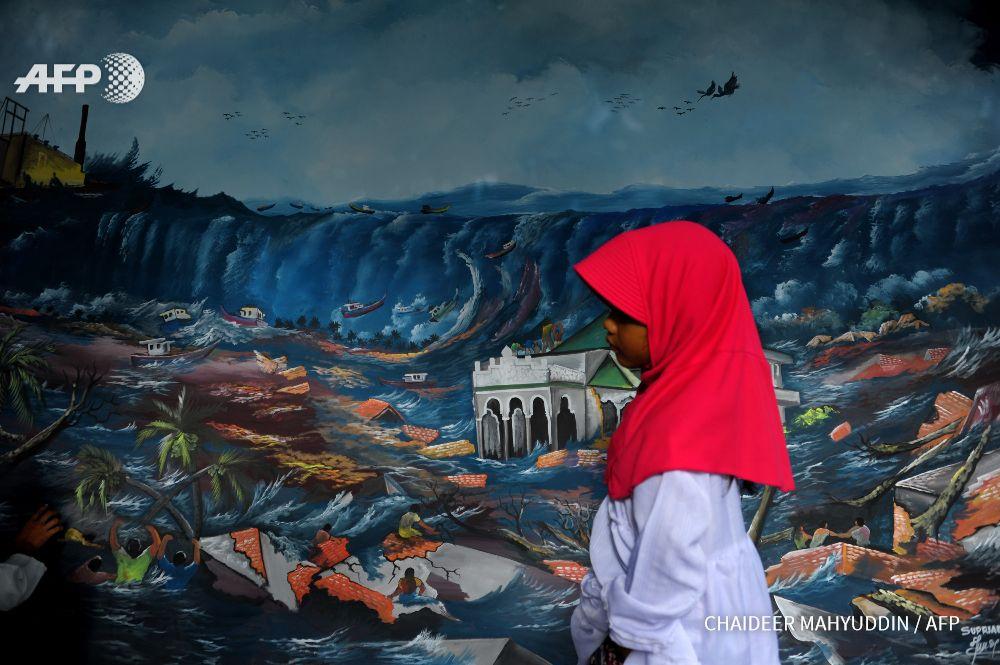 indonesia banda aceh a young acehnese girl walks past a tsunami
