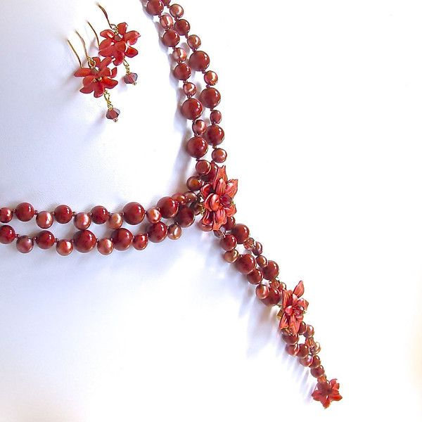 This extraordinary red statement necklace set, inspired by 1920's glamour features Marsala pearls and flower pendants. This ensemble is available online .
