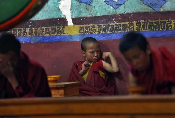 A young Buddhist monk flexes his muscles during morning prayers at Thikse Monastery in Ladakh, Indian-Administered Kashmir, May 7, 2014. © Ahmad Masood/REUTERS