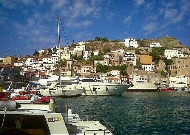 Serene view of the crescent shaped port of Hydra,Greece (island). I took this photo August 2010 with my cellphone. The weather was perfect during my 3 week vacation. No motor vehicles are permitted on the island.. Donkeys,horses & mules transport most supplies You can take the low cost water taxi to visit other villages. We enjoyed the beach at Mandraki...20 minutes away. View my personal photos from Greece. Click photo and view 'Slideshow' Full Screen. 1great-trip.com