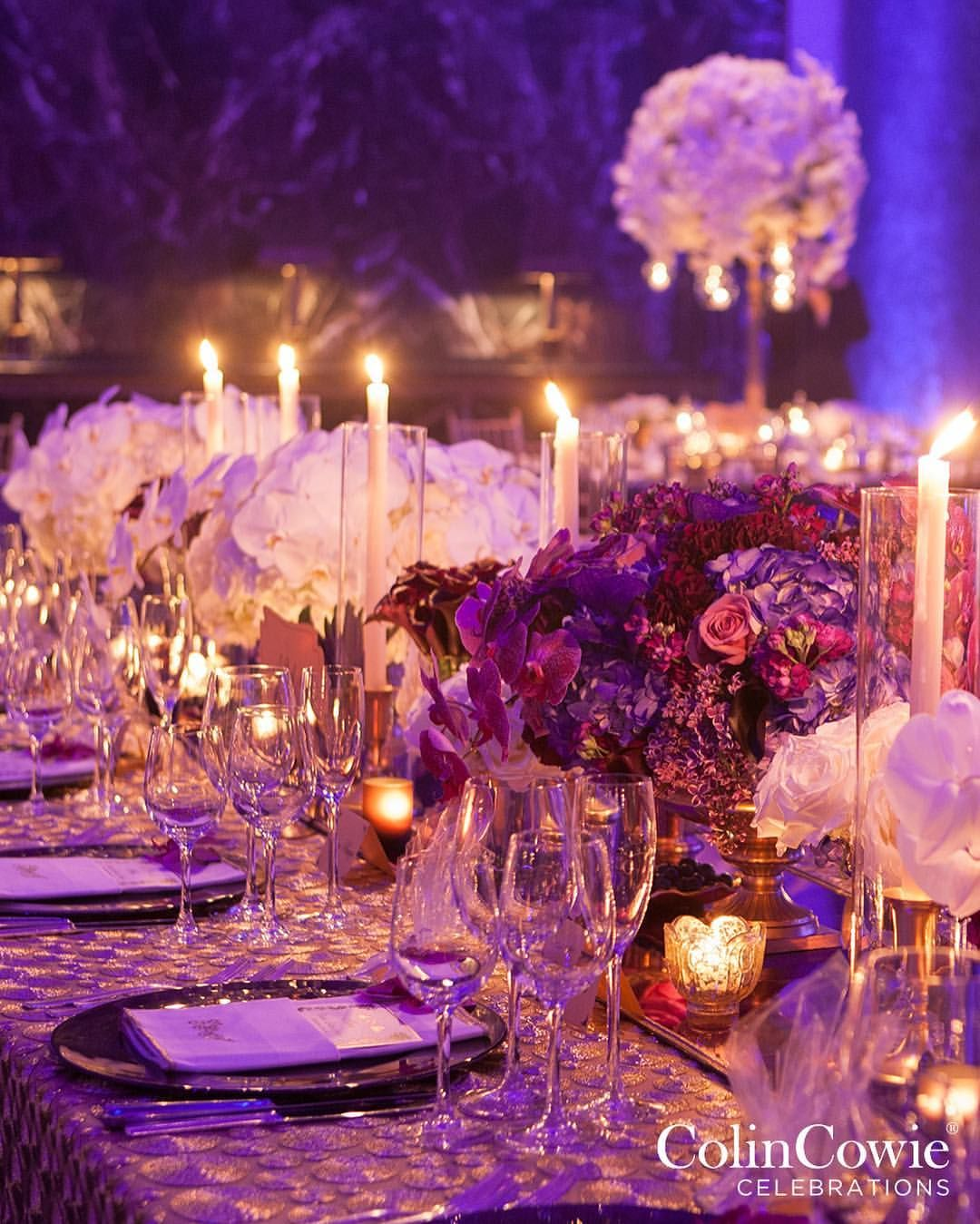 Tables are overflowing with white and purple orchids, accented by ...