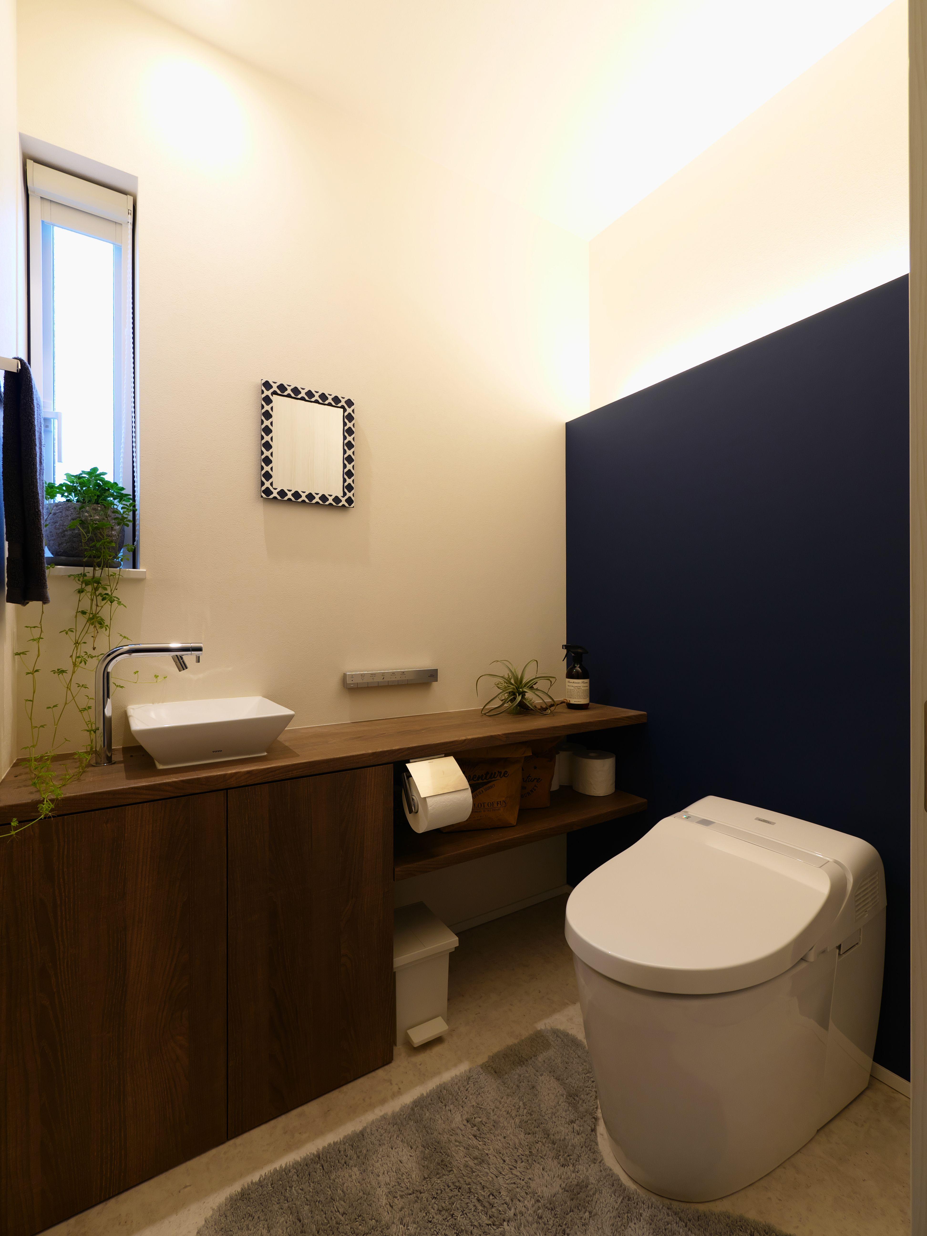 横幅をゆったりと広くとったトイレは 白とネイビーと木目の3つの色合わせ 間接照明で雰囲気がガラリと変わります クッションフロア サンゲツ Hm 6007 アクセントクロス リリカラ Lw 2585 カウンター収納 扉 アイカ工業 メラミンポストフォ