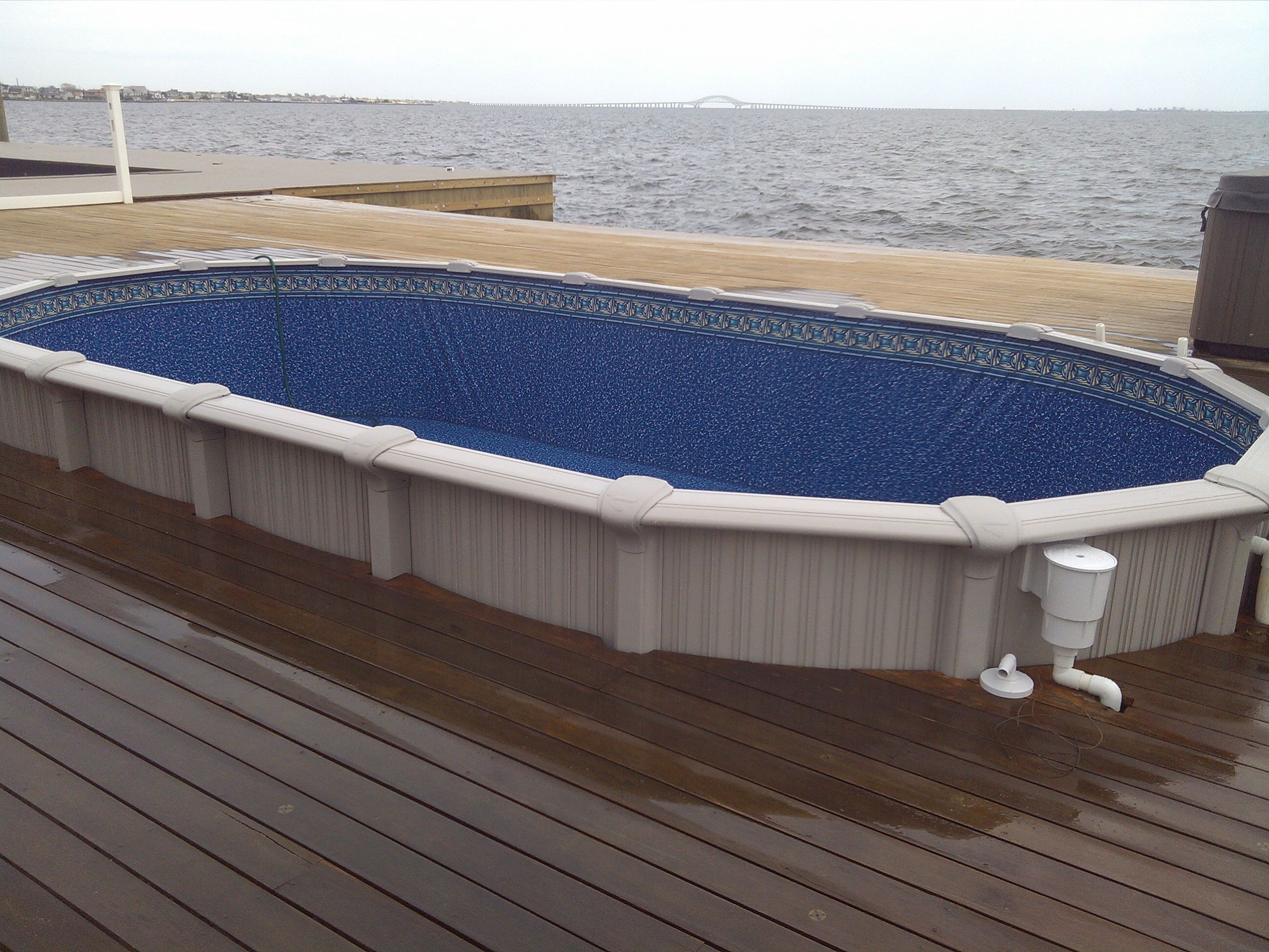 Sharkline Semi Inground pool with deck built around it ...