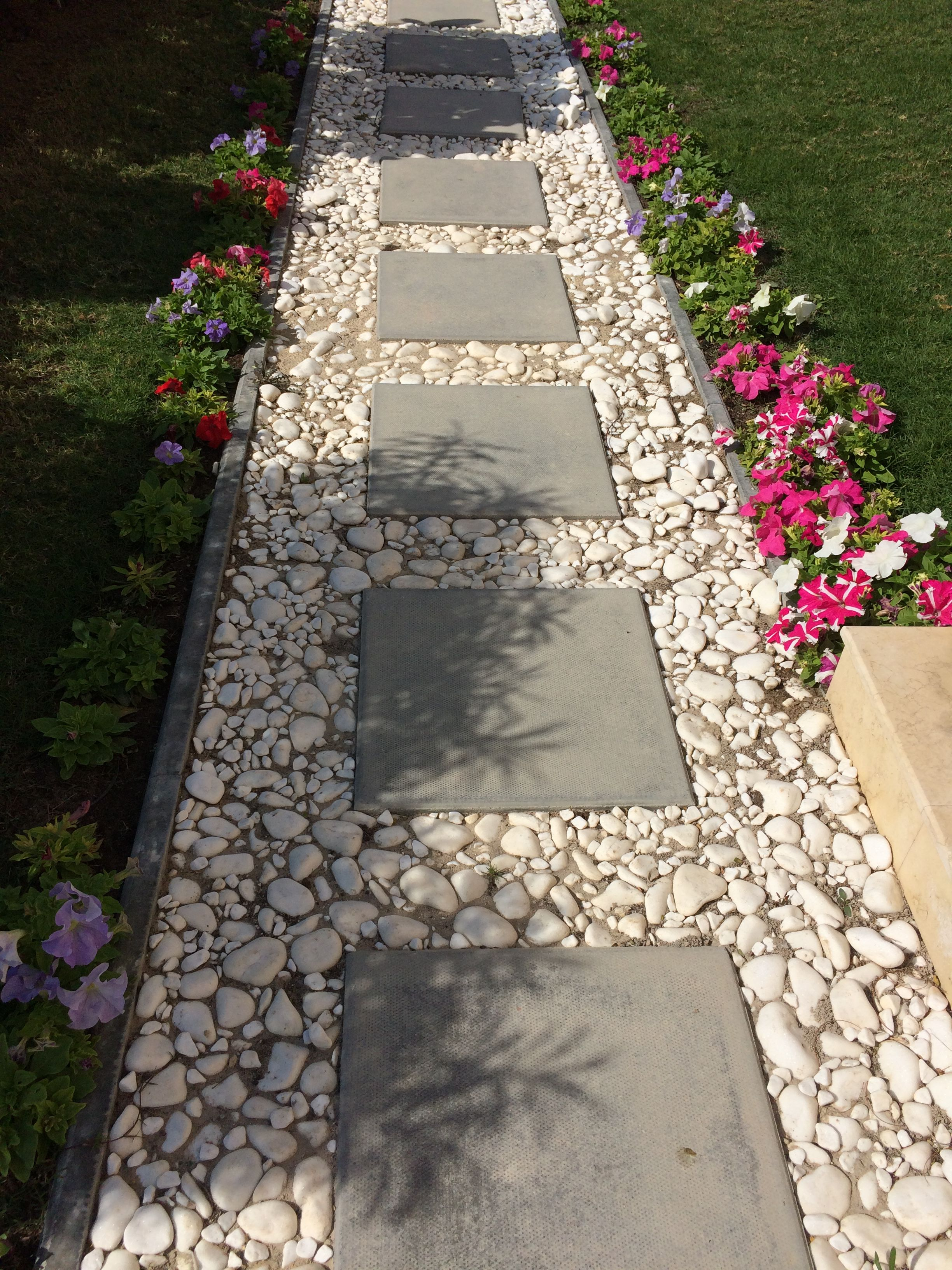 Cement block tiles bordered by white pebbles for a simple for Easy garden path ideas