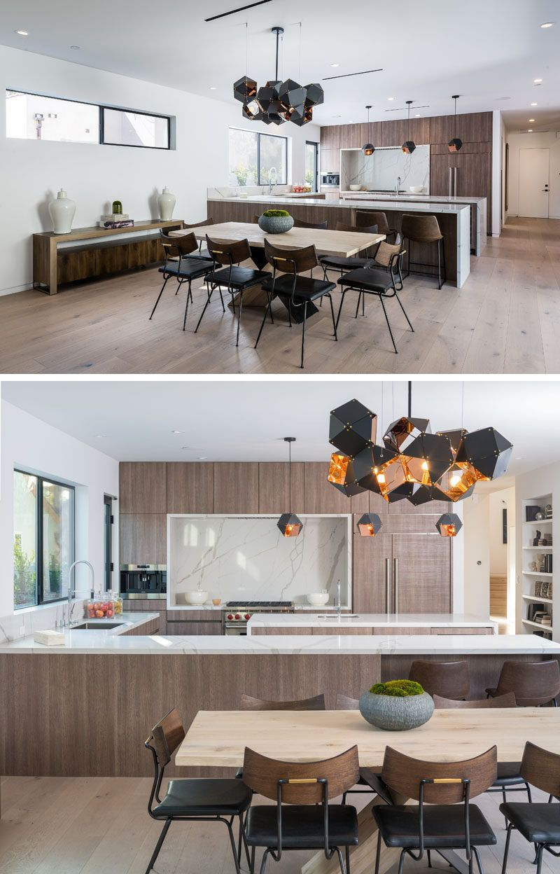 A modern and geometric chandelier sits above the dining table and anchors it in the large open plan room diningroom lighting