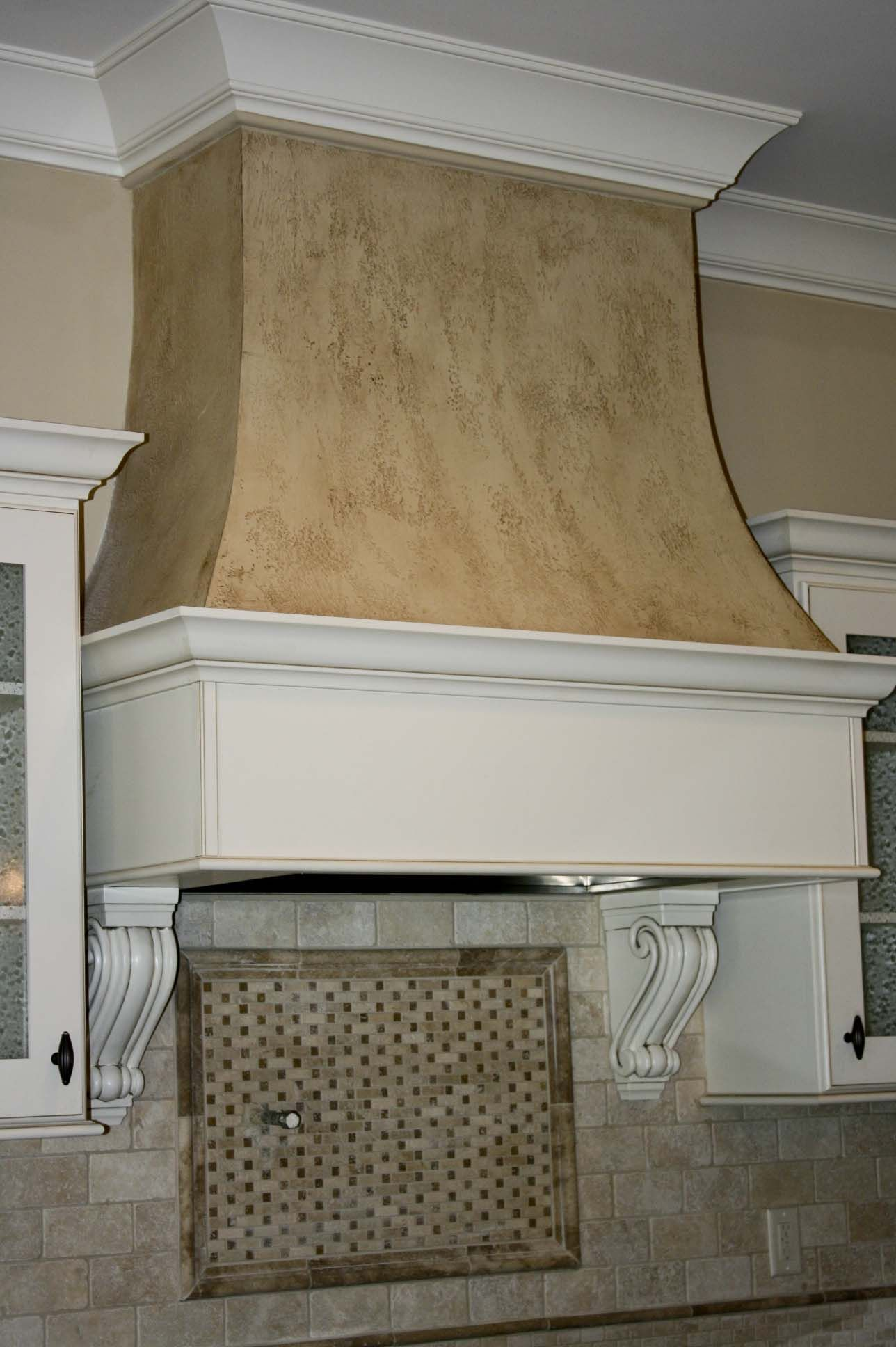 Custom curved drywall range hood with faux finish with cabinet matching  trim and corbels.
