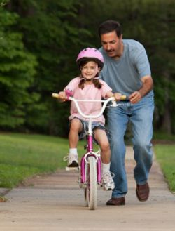 Father And Daughter Learning To Ride A Bicycle Bike Ride