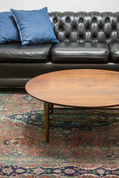 Tufted black leather sofa with denim throw pillows round mid century modern wood coffee table and fuchsia blue persian rug via birch  brass vintage also our collection of rental furnishings pinterest