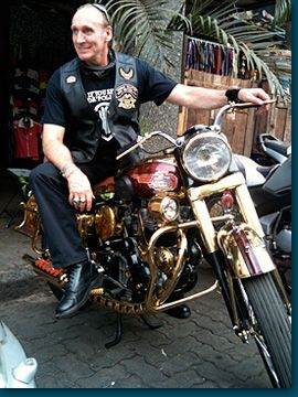 """Gregory David Roberts, author of Shantaram, on a bike designed and built at charity initiative, """"Happy Cycles,"""" in Bombay"""