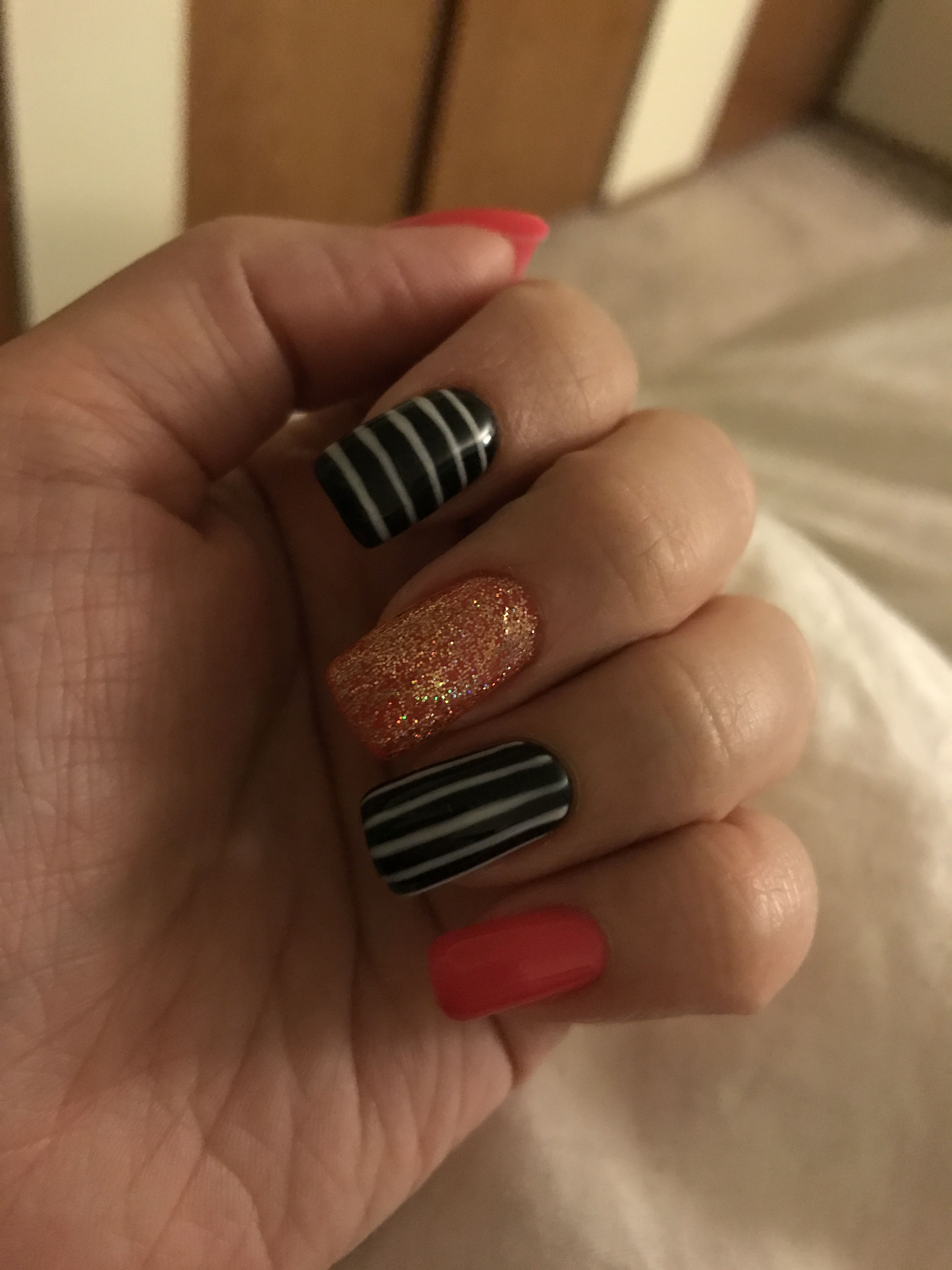 Striped nails with glitter and hot pink.