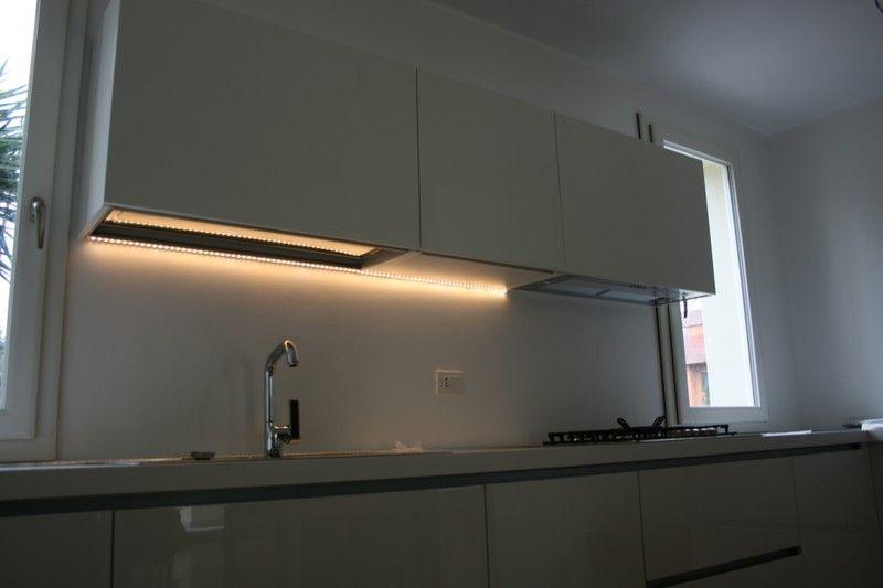 il piano di una cucina illuminato da una barra led a luce calda ...