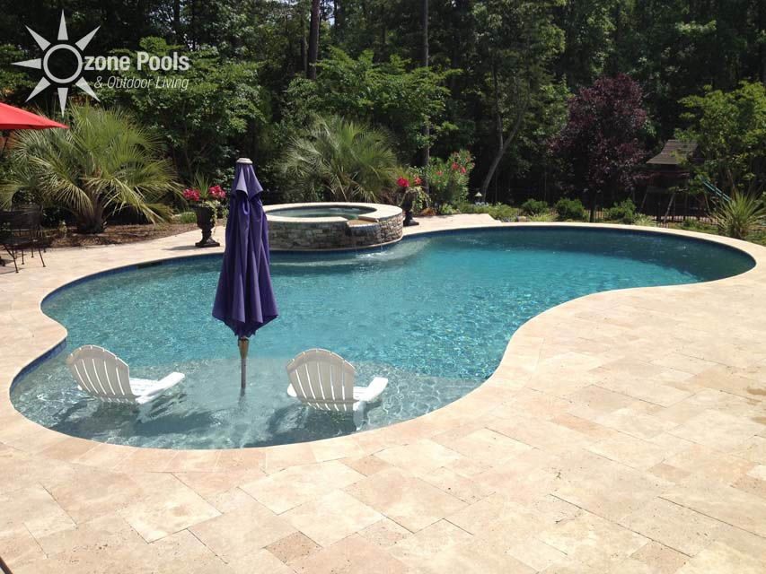 Freeform pool spa travertine decking pool outdoor for Pool design with tanning ledge
