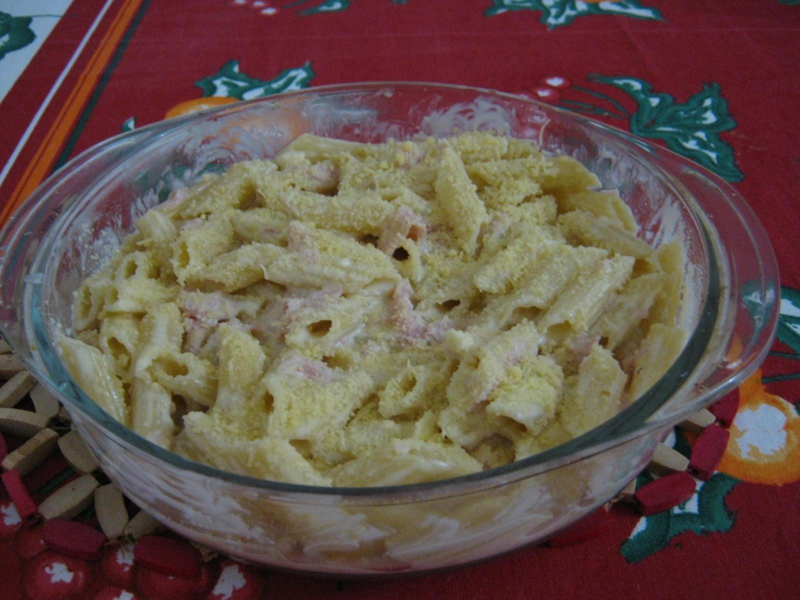 2 xícaras de macarrão penne cru  - Água para cozinhar o macarrão  - 1 caixinha de molho branco (200 ml)  - 1/2 colher de sopa de margarina ou manteiga  - 1/2 colher de sopa de cebola bem picadinha  - 1 pitada de nozmoscada ralada  - 50 g de presunto cortado em tirinhas  - 50 g de mussarela cortado em tirinhas  - 1 unidade de queijo polenguinho (1 cubo) cortado em pedacinhos  - Queijo parmesão ralado grosso para polvilhar  -
