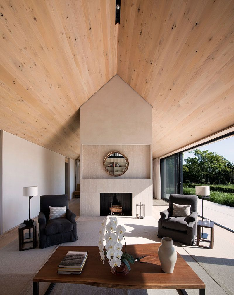 Inside this modern house wood covers the ceiling and oak has been used for the floor while sliding glass doors open the interior spaces to the patio