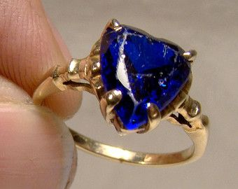 A 14k yellow gold genuine aquamarine and blue sapphires ring is an ultra modern setting circa 1970s. This vintage size 7-1/2 or 7.5 aqua blue gem stones ring is 1-1/4 x 7/16 across the setting and the aqua stone is 60 points or .6 carats (calculated) and the deep blue sapphires are 4 points each (by gauge). This stylish beauty weighs 3.8 grams and it is stamped 14K GENUINE GEMS along with a makers mark. This ring is in excellent vintage condition with no chips, cracks, dents, b...