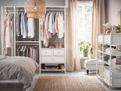 Mellemstort soveværelse med åben opbevaring fra gulv til loft med hvide hylder, garderobestænger, skuffer og stolper.