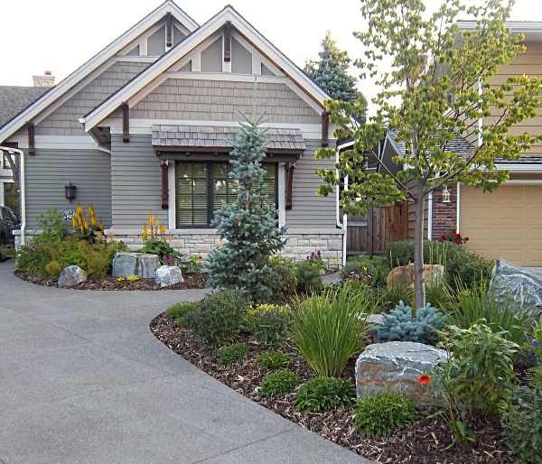 a very nicely done front yard rock garden with mulch this