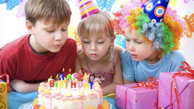 enfants autour d'un gâteau d'anniversaire pour souffler les bougies; fête d'anniversaire; enfants avec des chapeaux