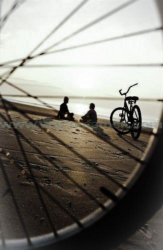 Composition!  Framing a bike scene/seen thru a bike tire... BRILLIANT!!!  Silhouette. Warm colors.  Sunlight.