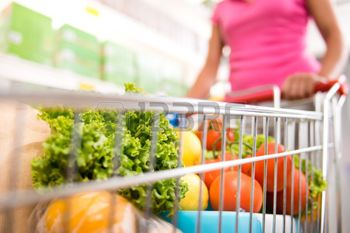 hands shopping vegetables: Woman at supermarket pushing a shopping cart filled with fresh fruit and vegetables. Stock Photo