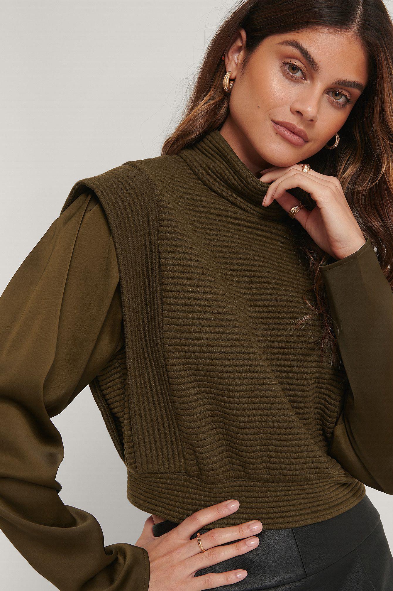 Dieser Pullover hat einen Rollkragen mit zwei Knopfverschlüssen auf der Rückseite, gesteppte Schultern, lange Ärmel aus Satin, ein strukturiertes, gestreiftes Muster mit einem elastischen unterem Saum, eine gemütliche Passform und eine abgeschnittene Länge. Passt perfekt zu deiner Boss-Stimmung.