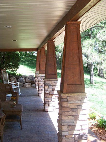 Stained Wood Paneled Tapered Atop A Stone Pedistal Porch