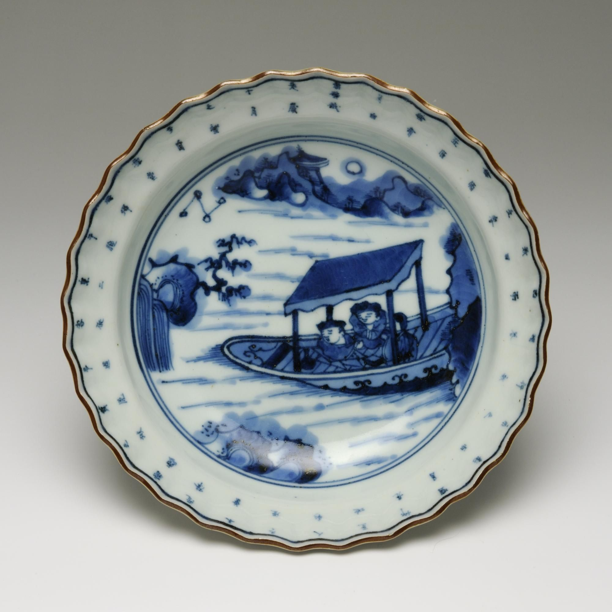 Circular dish of porcelain with fluted rim, decorated in underglaze blue with picture of two men in a covered boats near cliffs: Japan, 18th - 19th centuries, K.2005.592