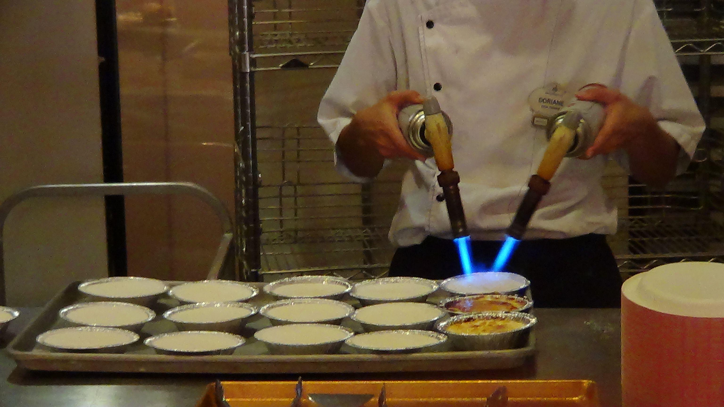#DisneyDining A chef at Les Halles Boulangerie at Epcot's France Pavilion prepares some Créme Brûlées.