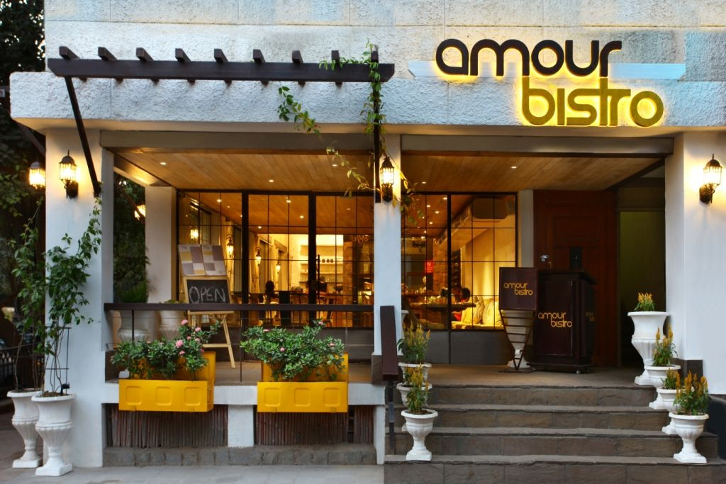 Amolur Bistro New Delhi Wooden Pergola And Bright Yellow Planters