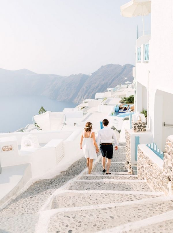 Couple walking hand in hand along the quaint streets of Santorini | Ilaria Petrucci Photography on @blovedblog via @aislesociety