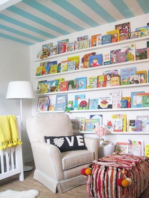 I'm a big fan of stripes on a nursery ceiling - such a fun way to provide some visual interest for your little one. But the bookshelves/display are the scene-stealing element in this room. What a great way to add some color and art, while also being functional!