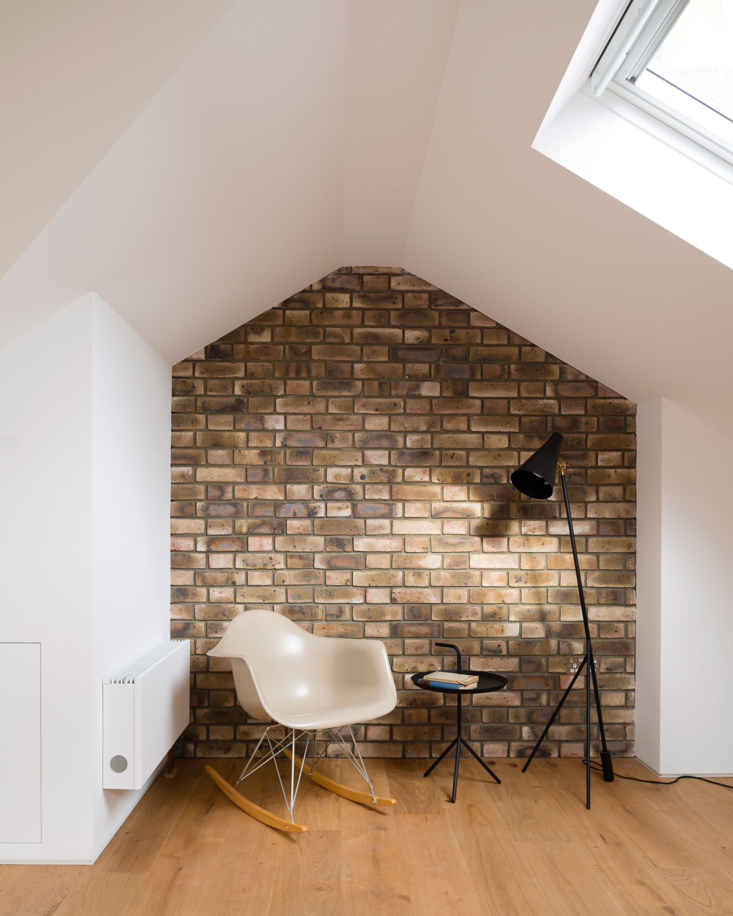 A reading nook with exposed brick wall and skylight project escape to the roof by a small studio