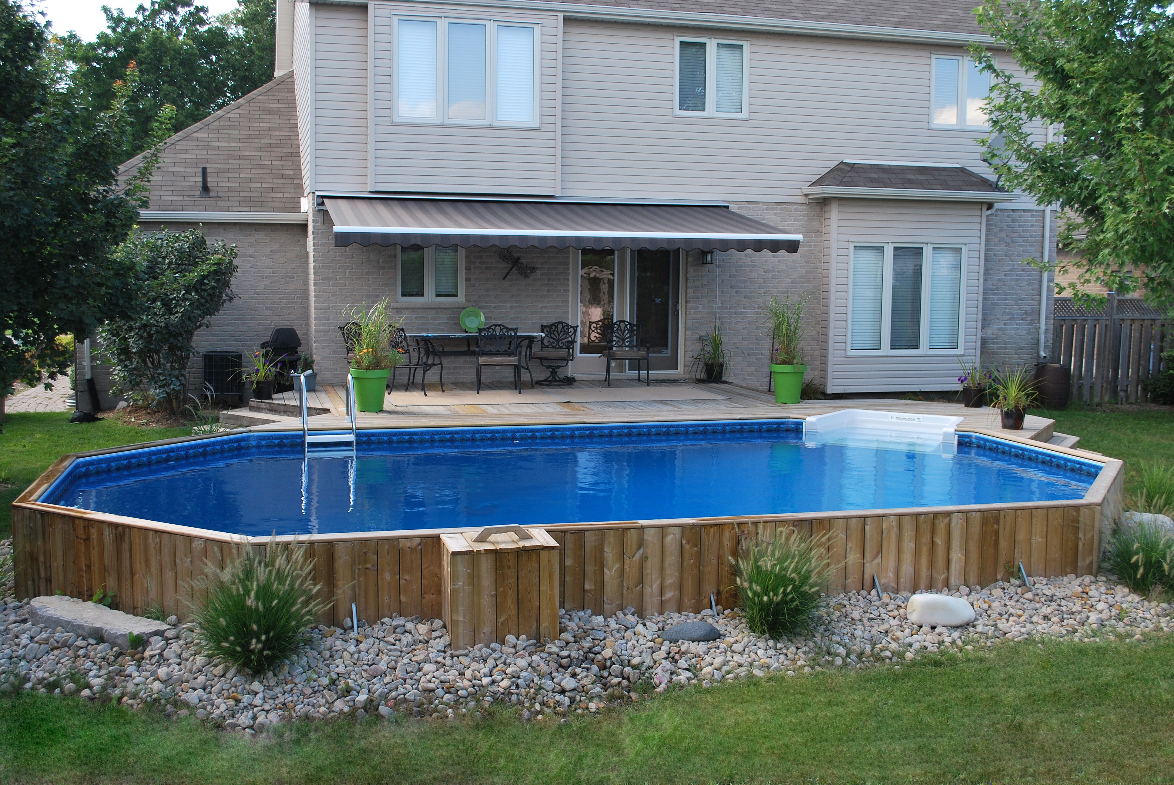 Semi inground or onground vinyl pool surrounded by wood for Above ground pool vinyl decks