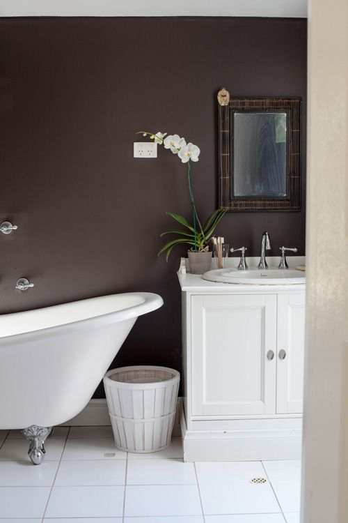 This white clawfoot tub stands out against the brown wall, making a huge  visual statement · Dark Brown BathroomDark ...