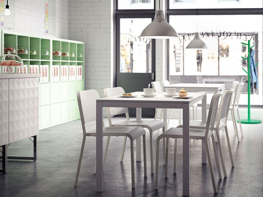 Kaviareň s bielymi stoličkami a stolíkmi a svetlozelenými policovými dielmi