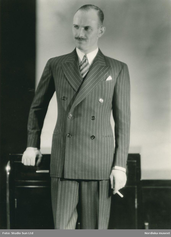8b4a6bdc74db Porträtt av man i kritstrecksrandig kostym och cigarett i handen. Fotograf:  Studio Sun Ltd