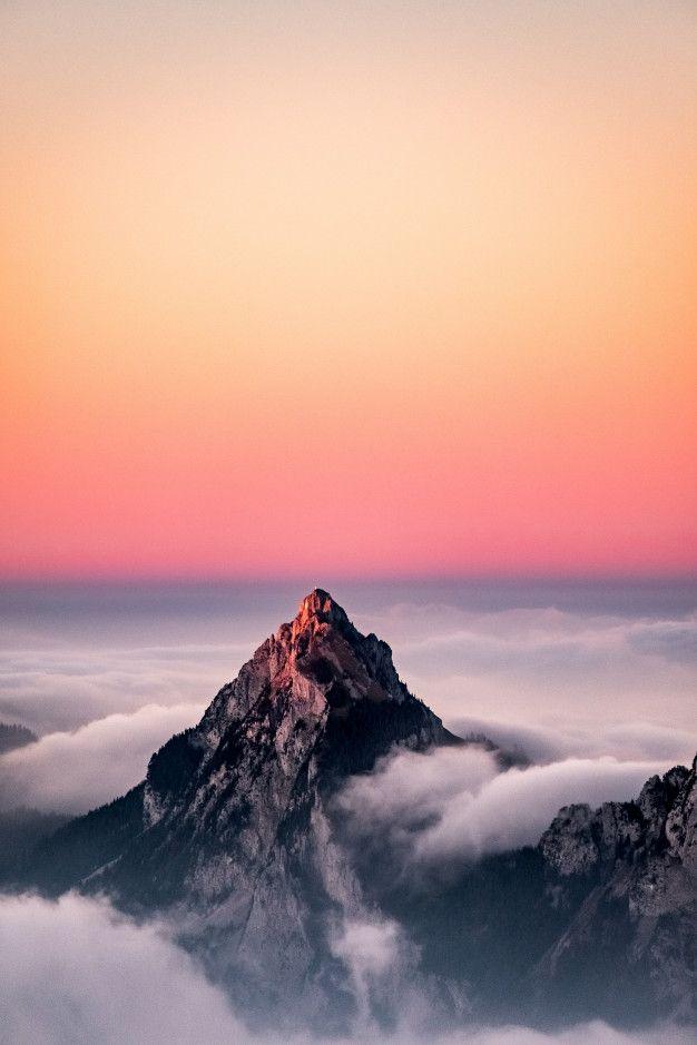 Téléchargez Vue Aérienne D'une Montagne Couverte De Brouillard Sous Le Beau Ciel Rose gratuitement