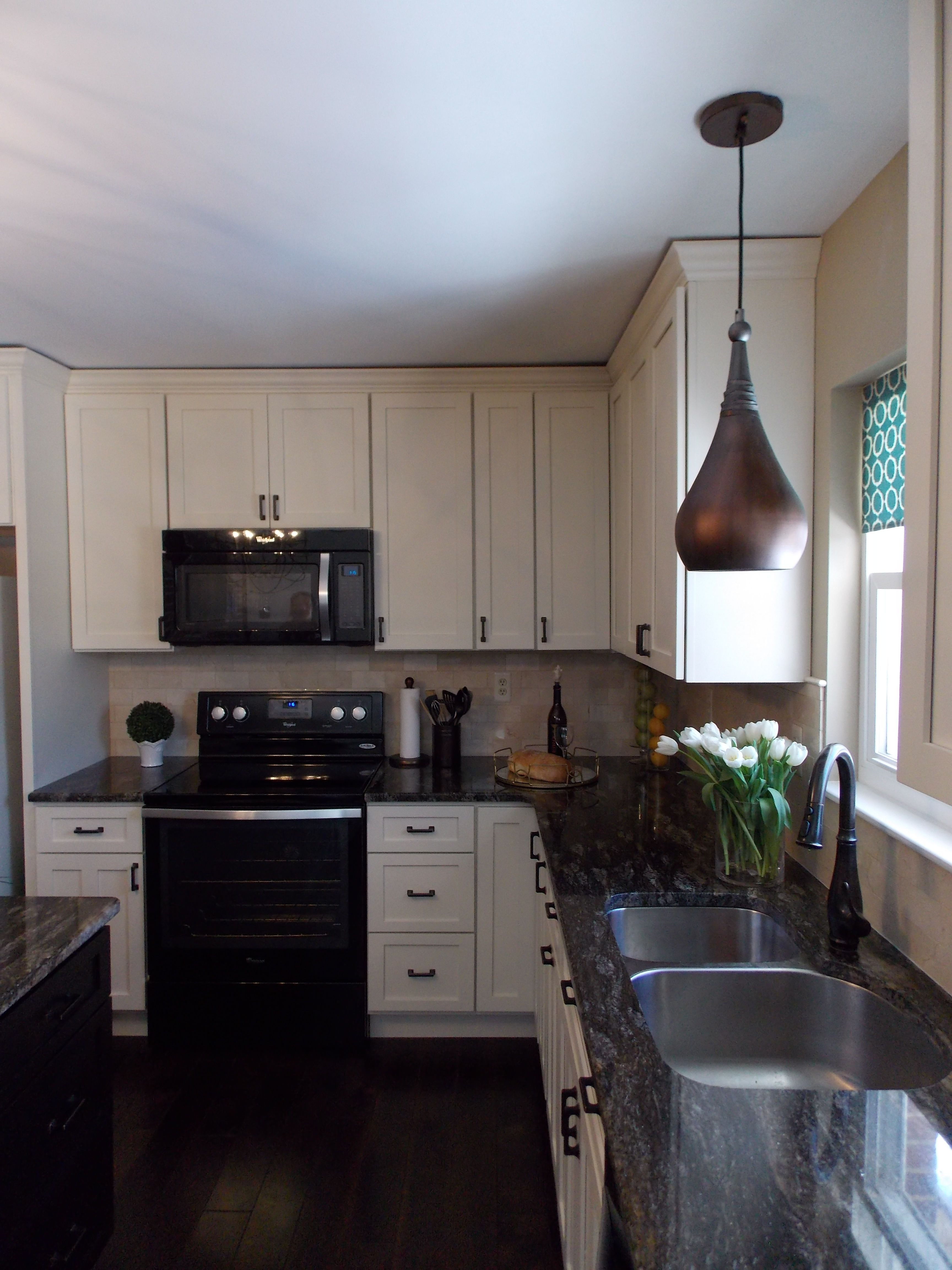 Kitchen with cream cabinets and saturnia schist countertops. Be ...