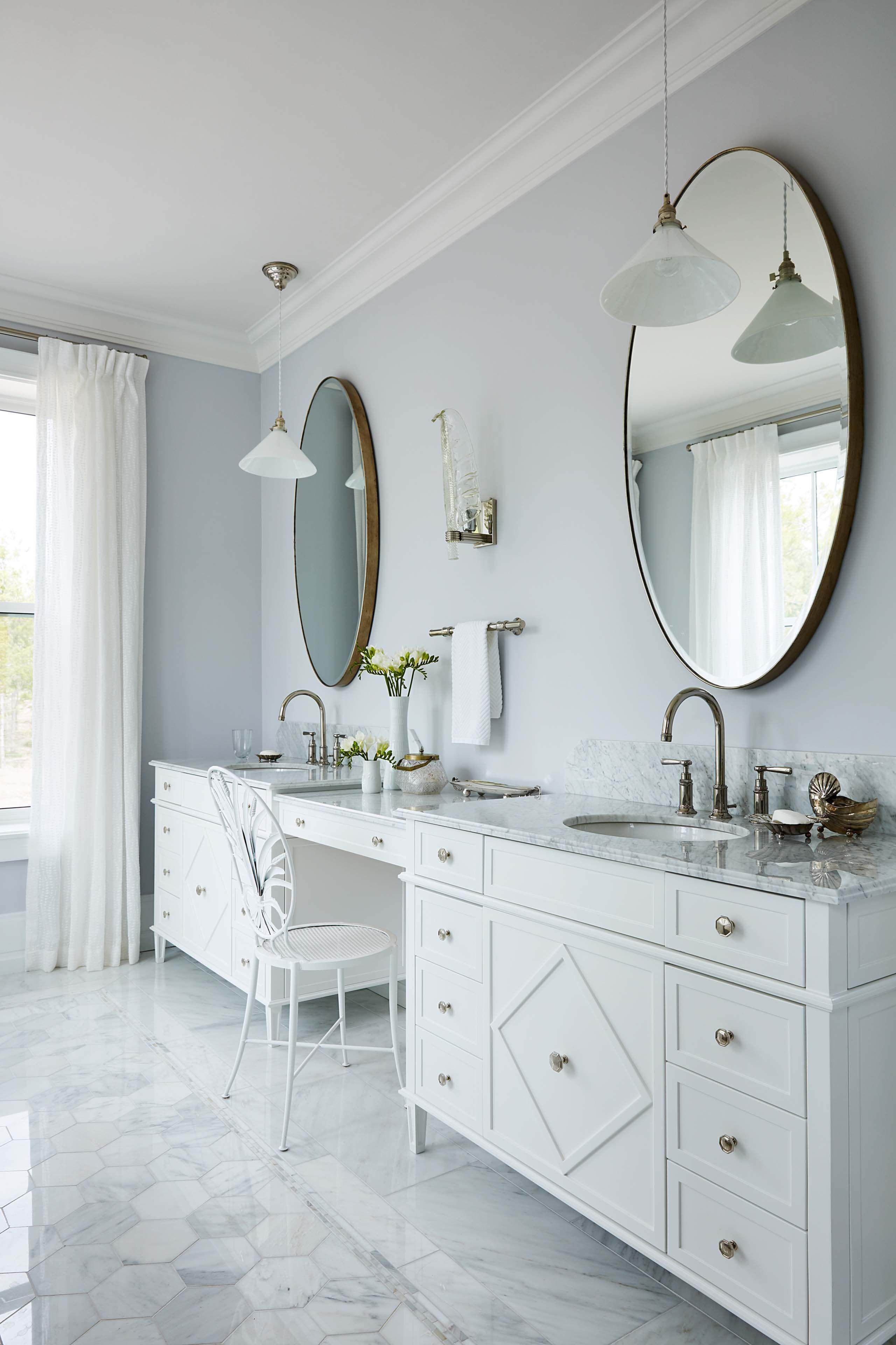 Elegant double vanities in serene marble bath with round ...