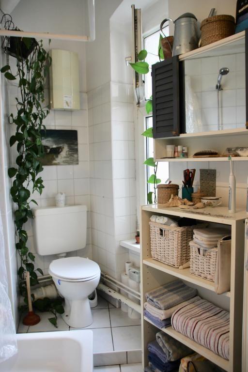 Schönes Bad mit weißen Fliesen, Regal und schönen grünen Pflanzen ...