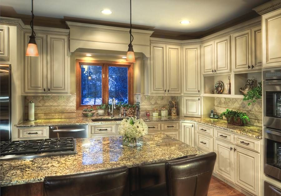 beautiful traditional kitchen with an ivory travertine backsplash and