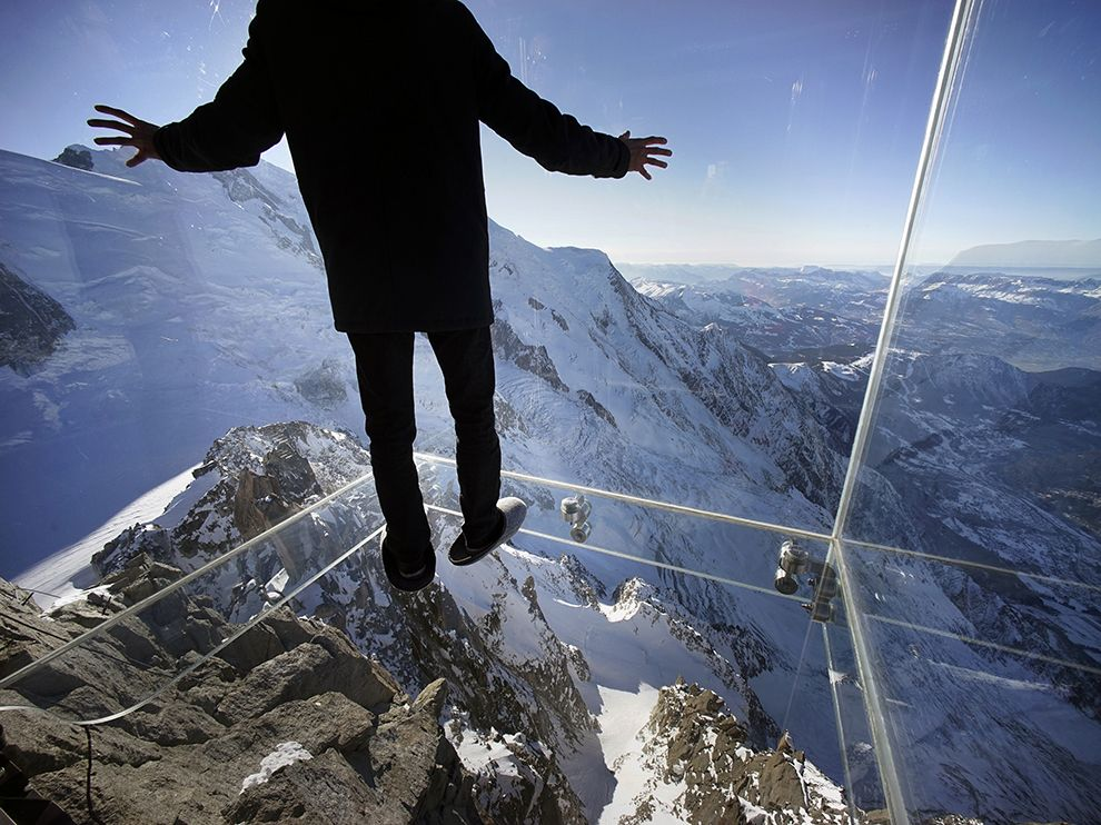 """Chamonix Skywalk, France: A journalist stands in the just opened """"Step Into the Void"""" installation at the Aiguille du Midi mountain peak above Chamonix, in the French Alps. The Chamonix Skywalk is a five-sided glass structure installed on the top terrace of the peak with a 3,280-foot drop below"""