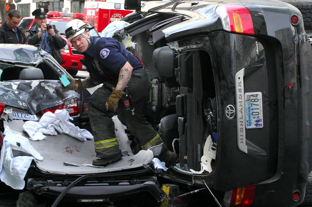 A Seattle firefighter exits the SUV involved in a crash on