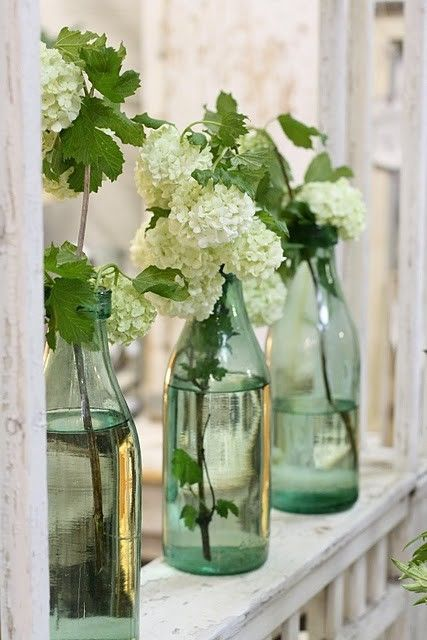 Floral Arrangement ~ simple hydrangeas in blue bottles form charming vignette